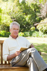 Man with a serious expression looking to his side while holding a book