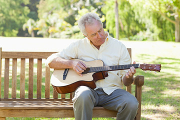 Man playing a guitar while sitting on a bench