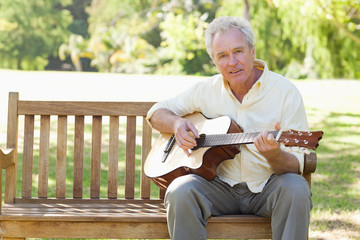 Man looks ahead while playing a guitar as he sits on a bench