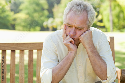 Man holding his face between his hands as he sits on a bench