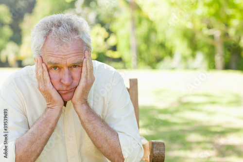 Man looks ahead while holding his face in his hands as he sits on a bench