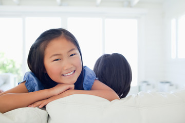Smiling girl facing the camera as her sister faces away