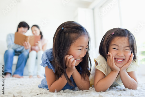 The parents look at a book as the girls smile while lying on the floor