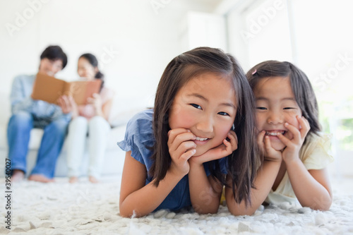 The parents look at a book on the couch as the girls smile on the floor