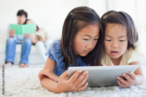 The parents read a book on the couch as the kids use the tablet