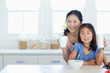 A mom and daughter at the table as the girl is about to eat cereal