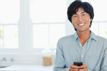 A man smiles and looks forward as he types on his phone
