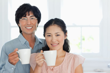 A couple stand together smiling with a cup in each ones hand