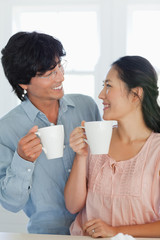 A couple look at each other as they hold a cup in hand