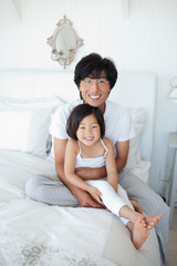 A girl with her dad holding her as they smile and sit on the bed