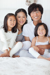 Close up of a family sitting on the bed while smiling
