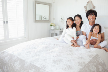 A family sits at the top of the bed holding each other