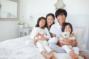 The family sit on the bed together with the girls holding teddy bears.