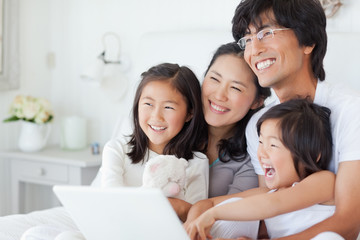 Side view of a family smiling with a laptop on the bed