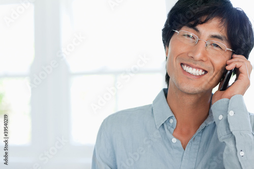 Man smiling as he talks on his phone