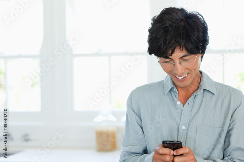 Smiling man texts on his phone