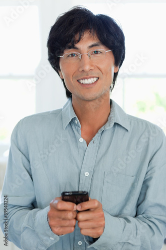 Close up of a man using his phone to text while looking forward