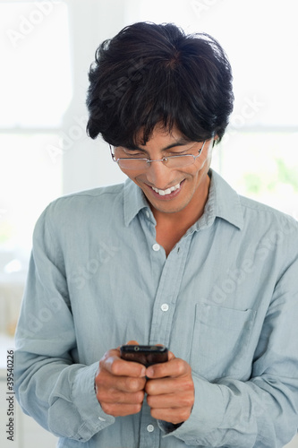 Smiling man looks at his phone as he sends a text