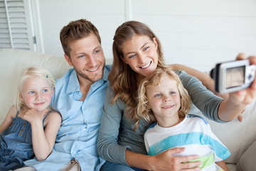 The family smiles and sit on the couch as they pose for a family photo