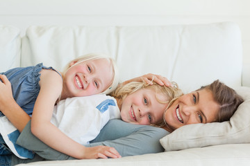 The mother lies across the couch with her son and daughter on top of her
