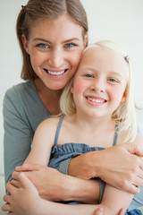 Close up of a smiling mother and daughter as they sit on the couch