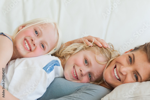 Close up of a mother and her kids lying across the couch