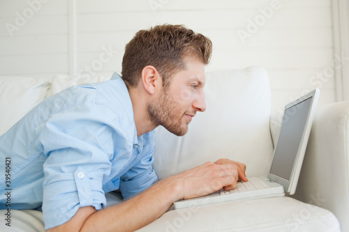 A man lying on the couch as he uses his laptop