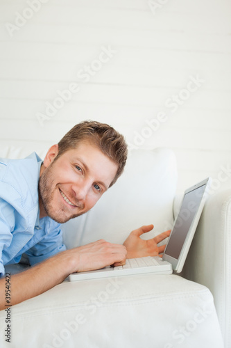 Close up of a smiling man as he uses his laptop