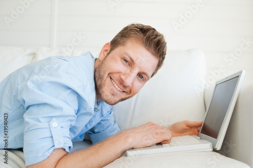 A smiling man looking ahead as he uses his laptop