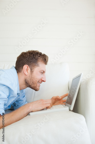 Man using his laptop as he lies across the couch and smiling