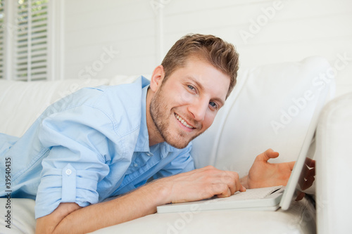 A man looking into the camera as he holds his laptop while lying across his couch