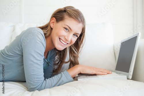 A smiling woman looks forward as she uses her laptop on the couch