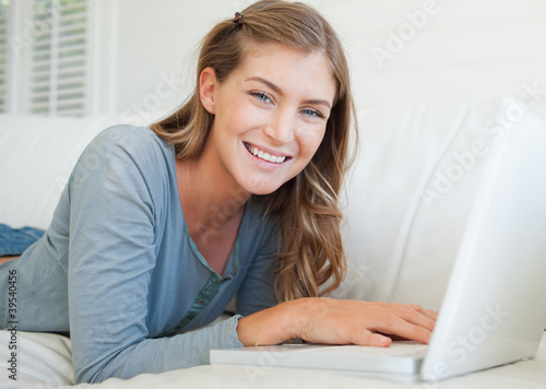 A woman looks at the camera smiling as she uses her laptop on the couch