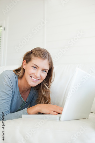 Close up of a woman using her laptop as she lies on the couch