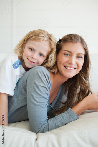 Close up of a mother and son smiling while lying on the couch