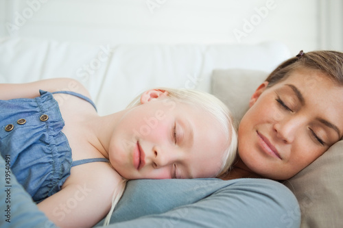 A mother and daughter calmly sleep on the couch