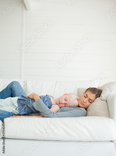 Mother and daughter asleep together across the couch