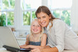 Mother and daughter smiling as they sit together by the laptop