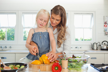 Mother and daughter cutting peppers together in the kitchen