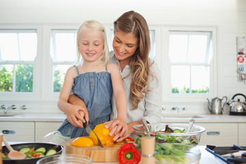 A smiling mom and child cutting peppers in the kitchen