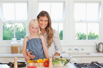 A mother and daughter smile and look forward while in the kitchen