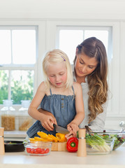 Mother guiding her daughter in how to cut peppers