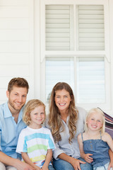A smiling family sitting outside on a wooden chair