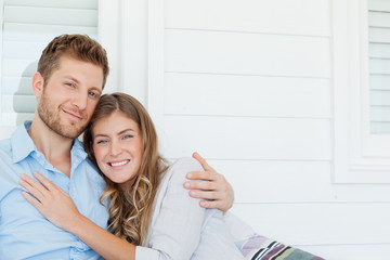 Man and woman together outside embracing each other and smiling