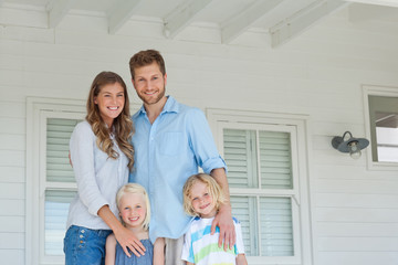 Happy family standing on the porch and smiling