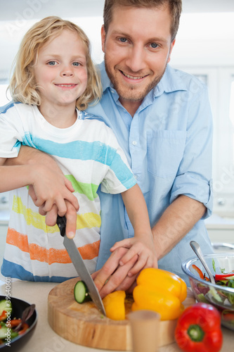A smiling father and son looking forward as they are about to cut food