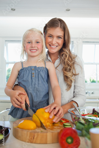 Mother and daughter cutting peppers and smiling