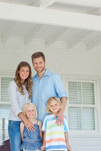 Family smiling happily as they stand on the porch