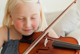 A girl plays the violin and listens to her music with her eyes closed