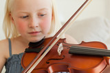A girl plays the violin and looks at the strings while she does,
